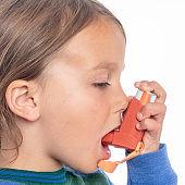 Little girl taking her asthma medicine