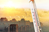 Thermometer against the background of a polluted city smog during hot weather.