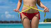 Sexy woman at the beach in bikini with measure tape. The concept of diet and healthy lifestyle.