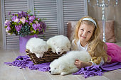 Blond girl posing with husky puppy white color in retro studio shoot. Cute young child play with puppy dogs in designed home decorations.