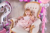 Princess baby girl celebrating life event wearing golden crown and pink airy dress. Cute girl posing in pastel colors studio shoot with air baloons and cake.