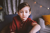 indoor lifestyle portrait of handsome thoughtful child boy