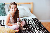 cute happy child girl relaxing at home on the bed in her room in early morning. Smiling kid with teddy bear enjoying cozy weekend.