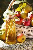 Basket with apples cider juice or vinegar in glass bottle