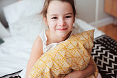 happy child girl sitting on bed and hugs pillow, waking up in early morning or going to sleep. Kid in comfortable room enjoying weekend