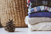 fall casual woman fashion clothes set. Stack of plaid shirts and knitted sweaters with pine cone and basket on background. Cozy stylish womanswear.