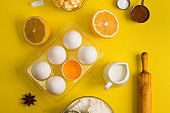 Baking flat lay background with eggs floor butter lemon sieve
