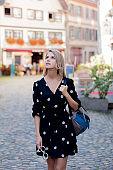 girl in black dress walking down the street in Strasbourg