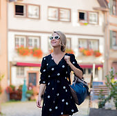 girl in black dress walking down the street in Strasbourgg