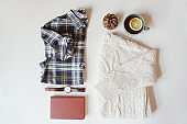 woman casual fashion set flat lay. Plaid shirt, knitted sweater, watch and book on white background. Stylish outfit top view.