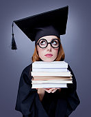 graduate girl in mantle with books