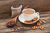 Coffee in a cup with coffee beans and cracker