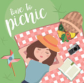 Summer picnic in meadow with food, drink and dreamy girl