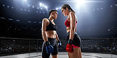 Female MMA fighters in professional boxing ring