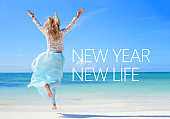 New year new life quote on the image of woman jumping in the air on the beach.