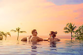 Happy couple on honeymoon in luxury hotel pool