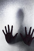 Spooky silhouette of trapped abused woman with hands pressed against glass window