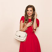 Smiling Fashionable Woman In Red Dress With Beige Purse