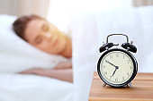 Alarm clock opposite of beautiful young woman sleeping while lying in bed comfortably and blissfully. Happy waking up early for a job.