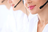 Unknown call center operators at work. Focus at beautiful woman lips