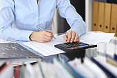 Female bookkeeper or financial inspector  making report, calculating or checking balance. Internal Revenue Service checking financial document. Audit concept in busines