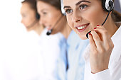 Call center. Group of operators at work. Focus at beautiful business woman in headset