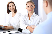 Business handshake by blonde woman and her partner at meeting. Concept of success and agreement