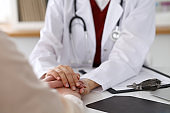 Closeup of a doctor and patient sitting at the desk. Medicine and health care concept