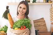 Young happy woman holding paper bag full of vegetables and fruits while smiling. Girl have made shopping and ready for cooking  in kitche