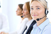 Call center. Group of operators at work. Focus at blonde business woman in headset