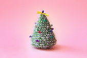 Knitted Christmas tree with multicolored pins on it.