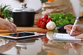 Closeup of human hands cooking in kitchen. Women discuss a menu using tablet computer. Copy space area at touch pad. Healthy meal, vegetarian food and lifestyle concepts