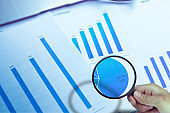 Business Analysis and Statistics Reports from sales charts last year using a magnifying glass.