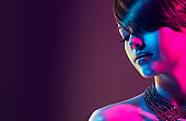 Sophisticated multi colored light on the face and shoulders of spectacular, young woman.
