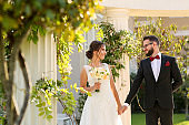 Beautiful wedding couple posing outdoor near luxury structure