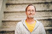 Outdoor portrait of 50 year old man wearing grey hoody and eyeglasses