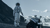Astronaut Goes on the Expedition to Explore Rocky Alien Planet. In the Background His Base and AI Powered Rover. Futuristic Colonization Concept.