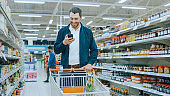 At the Supermarket: Handsome Man Uses Smartphone, Smiles while Standing at the Canned Goods Section. Has Shopping Cart with Healthy Food Items Inside. Other Customers Walking in Background.