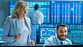 Stock Market Team Wins Big on Selling/ Buying Bonds. Senior Manager and Professional Trader are Happy. Ticker Numbers on Screen.