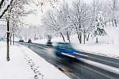 Motion blur of a blue car on winter road