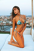 Beautiful brunette posing in a bikini on a sun chair