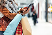 Young woman carrying paper shopping bags in modern mall and texting