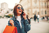 Beautiful young woman talking on the phone in the city after shopping