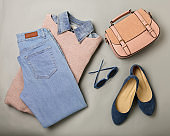 Flat lay of a casual woman fashion outfit - jeans, pink dress, handbag and sunglsses. Top view on gray background.