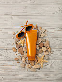 Suntan cream on a gray wooden background, sunglasses and shells, sea stones and a starfish.