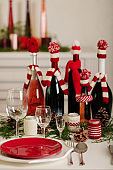 Merry Christmas and Happy New Year! Тable setting holiday knitted decor - Santa Claus knitted hats on the bottle with wine, candles in candlesticks in knitted decor.
