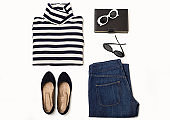 Fashion set of blue jeans, striped sweater, shoes and sunglsses on white background.