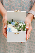 Woman holding wedding rings in wooden box decorated with flowers. Close horizontal photo