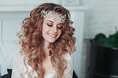 Happy young bride in tiara and lingerie laughing. Close portrait