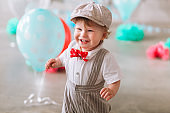 Happy baby boy celebrating first birthday. Kids birthday party decorated with balloons and colorful banner